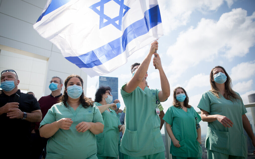 Israeli medical staff cheer an Israeli airforce acrobatic team flying over Ichilov hospital in Tel Aviv on Israel's 72nd Inependence Day. This year, the airforce will fly over all the hospitals in Israel as a way of honouring the medical staff during Covid-19